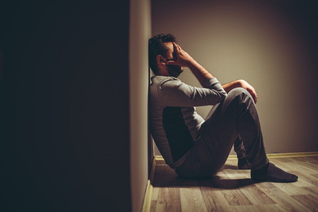 Young man with anxiety and depression sitting on the floor