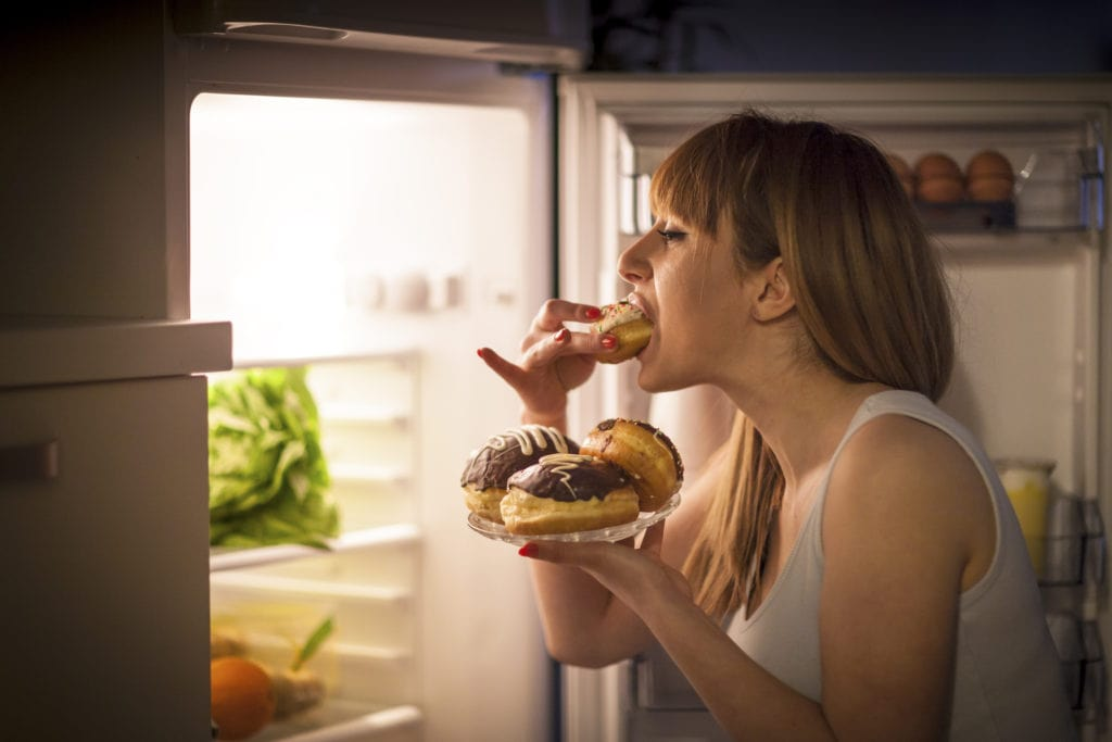 Woman with an eating disorder eating lots of food